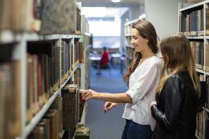 Studenki przeglądają regały w bibliotece