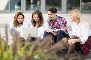 Studenci siedzą na schodach z laptopem